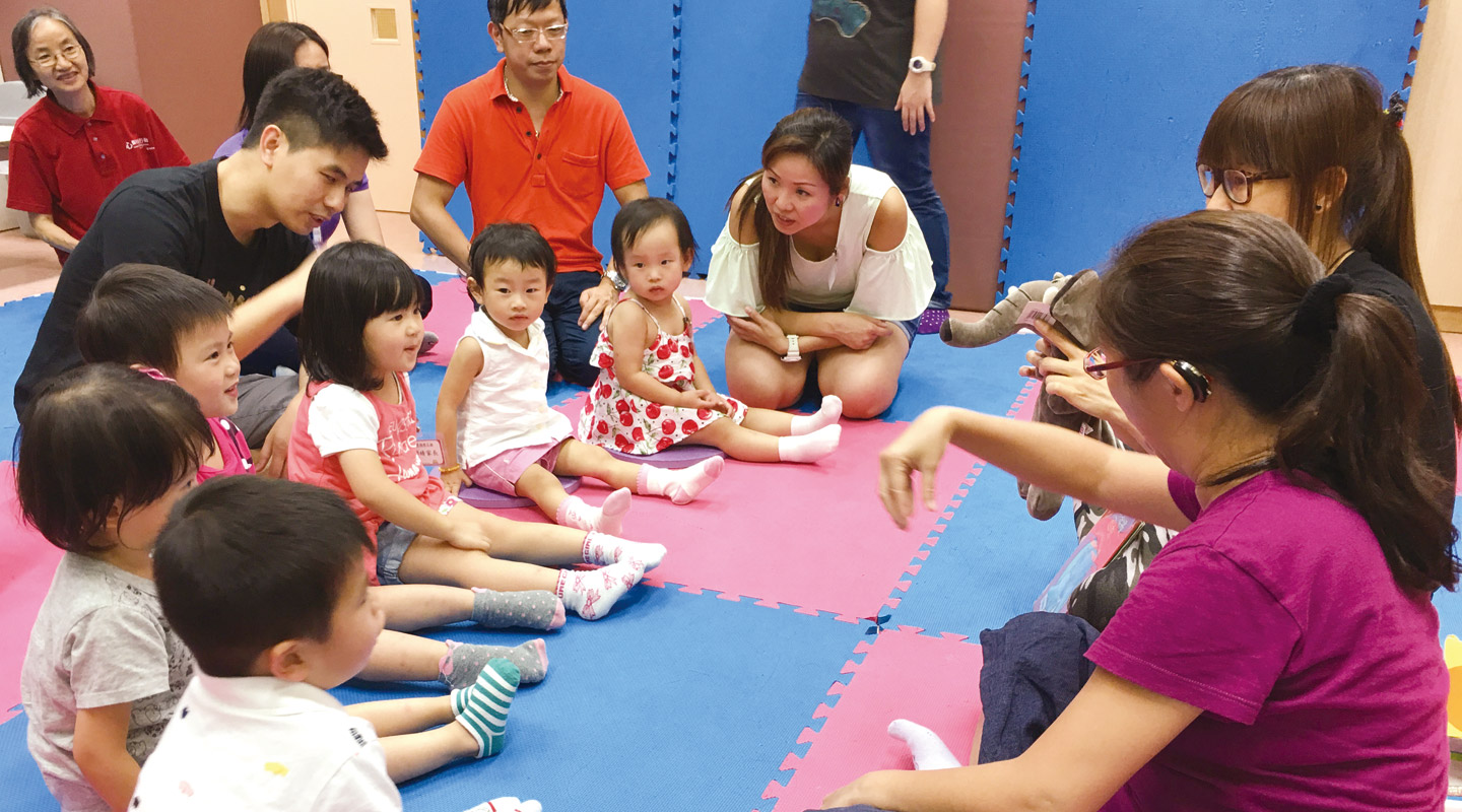 Toddlers and their parents engaging in a sign class led by a deaf and a hearing teacher