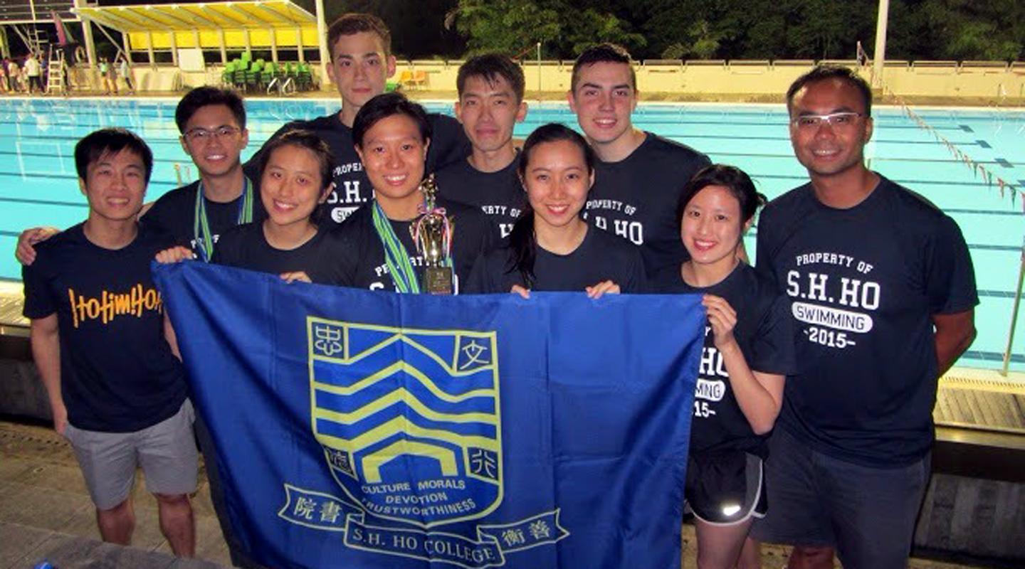 Rachel (holding the trophy) with swimming coach Mr. Clement Wu (1st right) and swimming team members of S.H. Ho College <em>(courtesy of Mr. Wu)</em>
