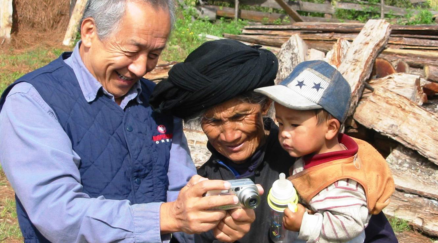 Prof. William S-Y. Wang shows a picture to a woman of Pumi ethnic minority